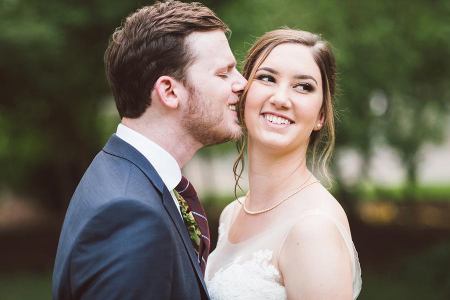 Groom kisses bride on cheek.