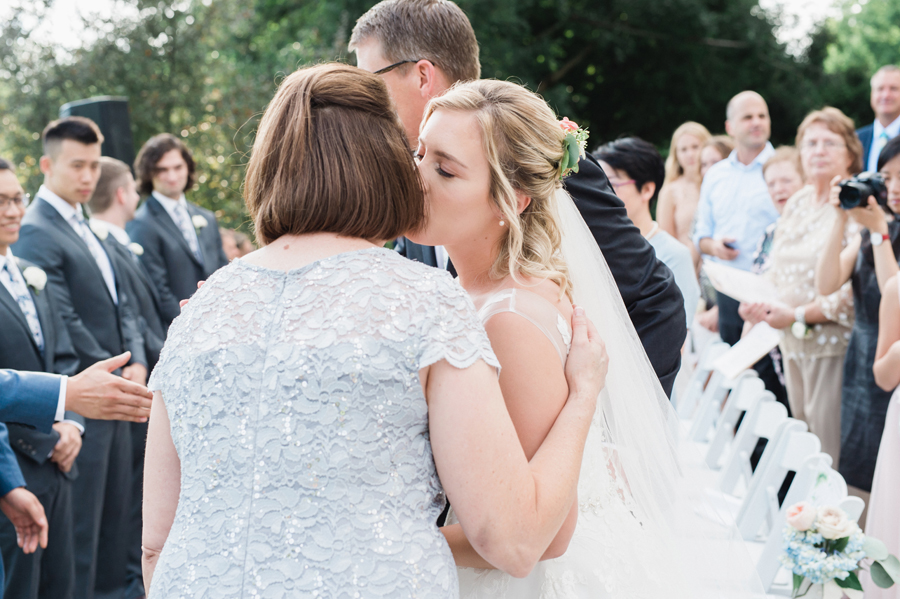 Bride kisses her mom at wedding ceremony.