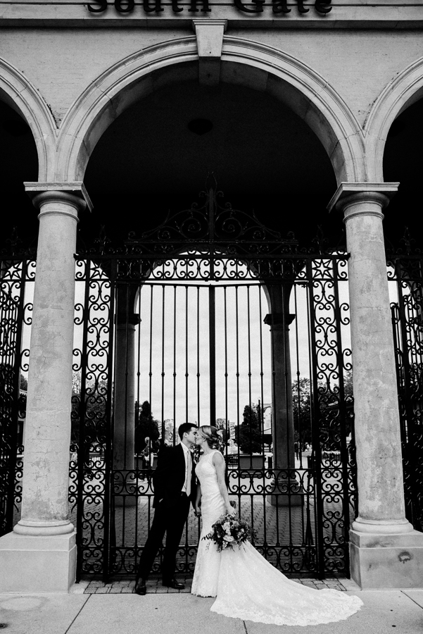 Bride and groom kiss in front of the South Gate at Brookfield Zoo.