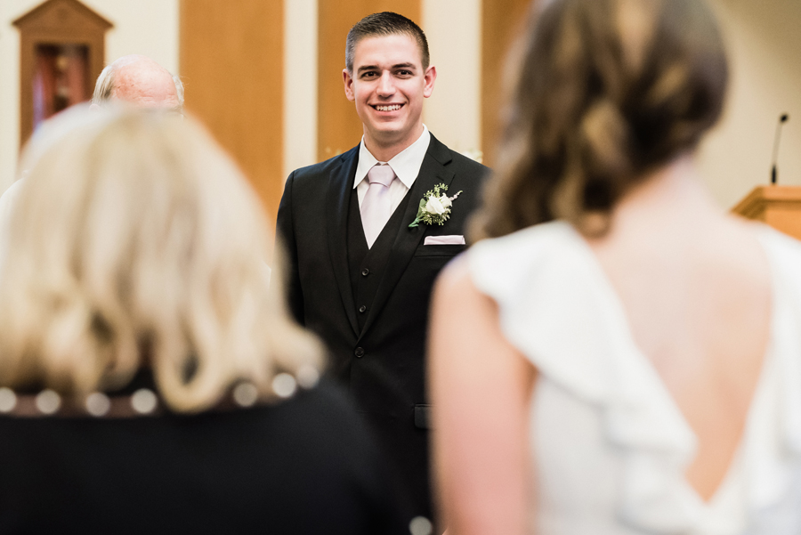Groom reacts to watching his bride walk down the aisle.