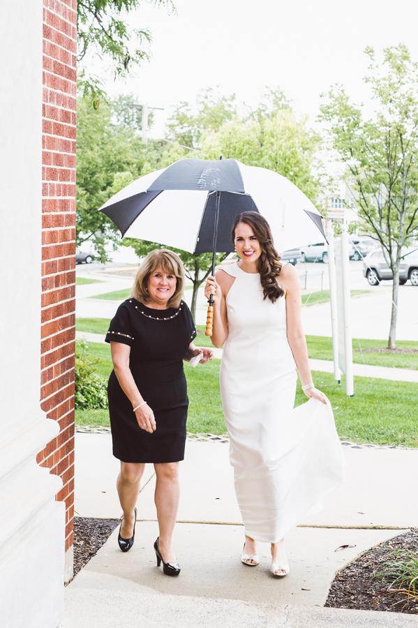 Mom walks bride into church on a rainy day.