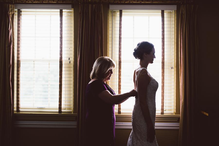 Mom helps her daughter get into wedding dress.