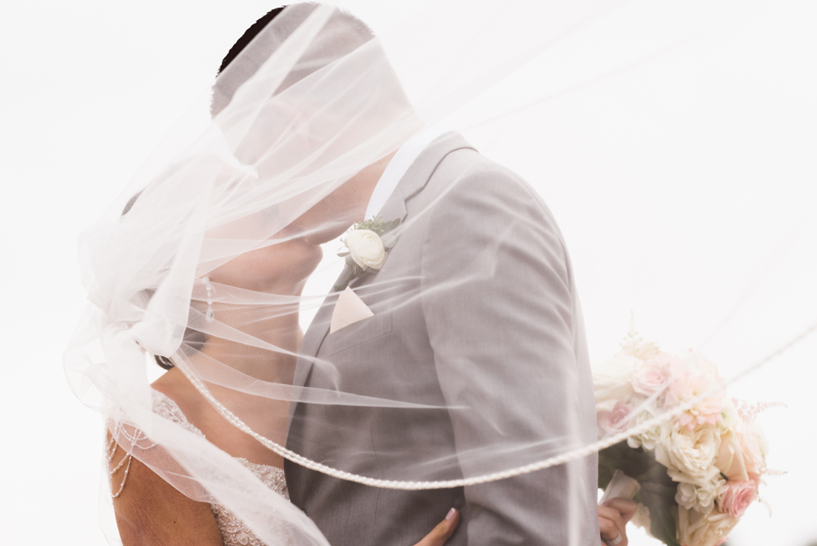 Bride and groom kiss under veil.