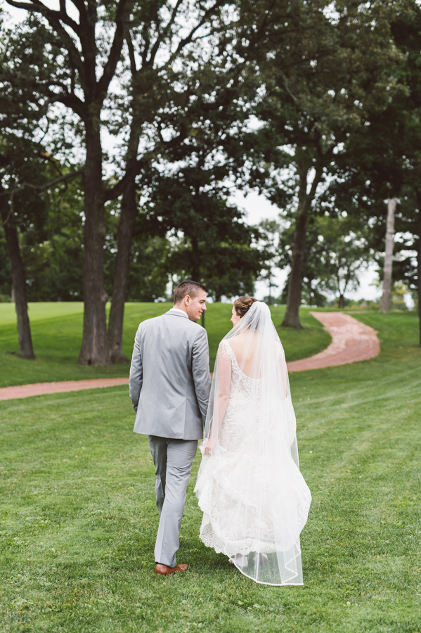 Bride and groom walk together on the golf course.