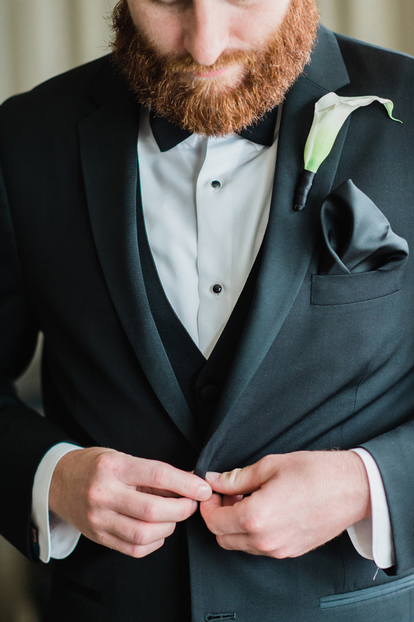 Groom buttons his jacket.