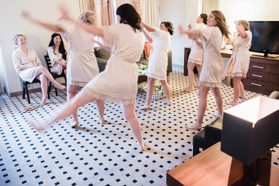 Bridesmaids dance in hotel room.