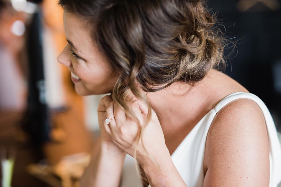 Bride puts her earrings on.