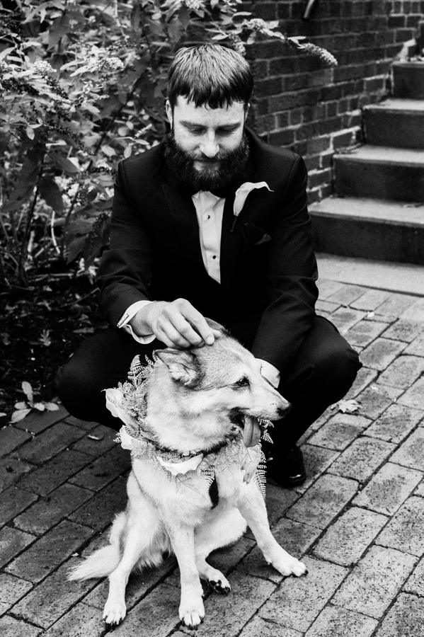 Groom pets his dog.