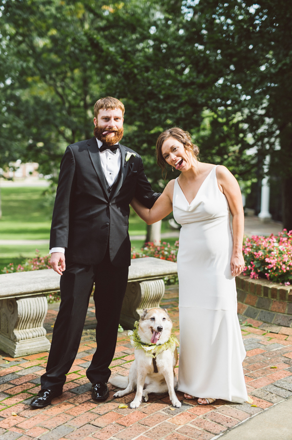 Bride and groom stick out their tongues like their dog.