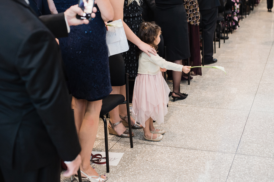 Girl holds flowers up for bride as she walks down the aisle.