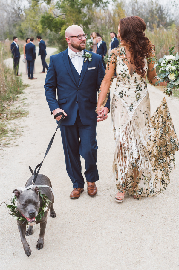 Bride and groom walk their dog.