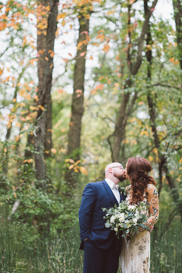 Bride and groom kiss in woods.