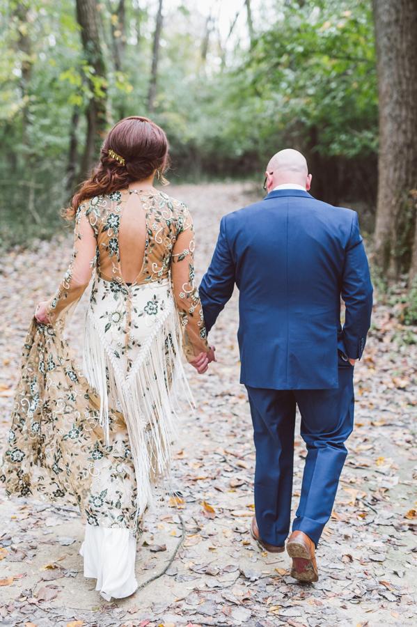 Bride and groom walking through woods.