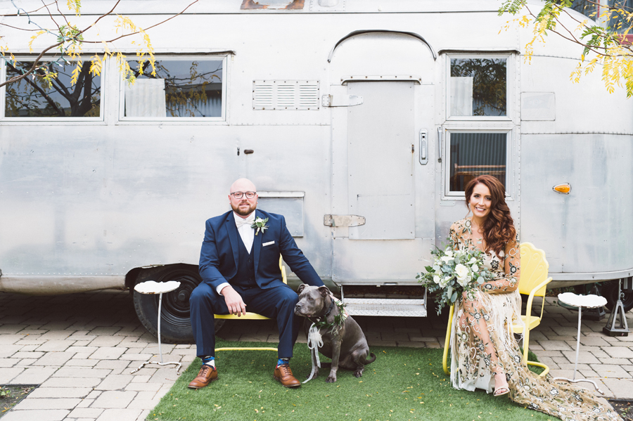 Bride and groom with airstream trailer.