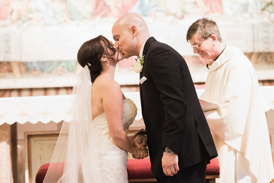 Bride and groom first kiss at wedding ceremony.