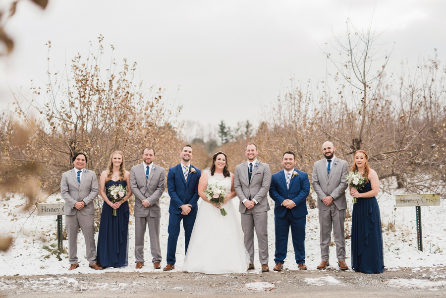 Portrait of bridal party in orchard.