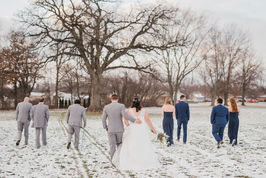 Bridal party walking in snow.