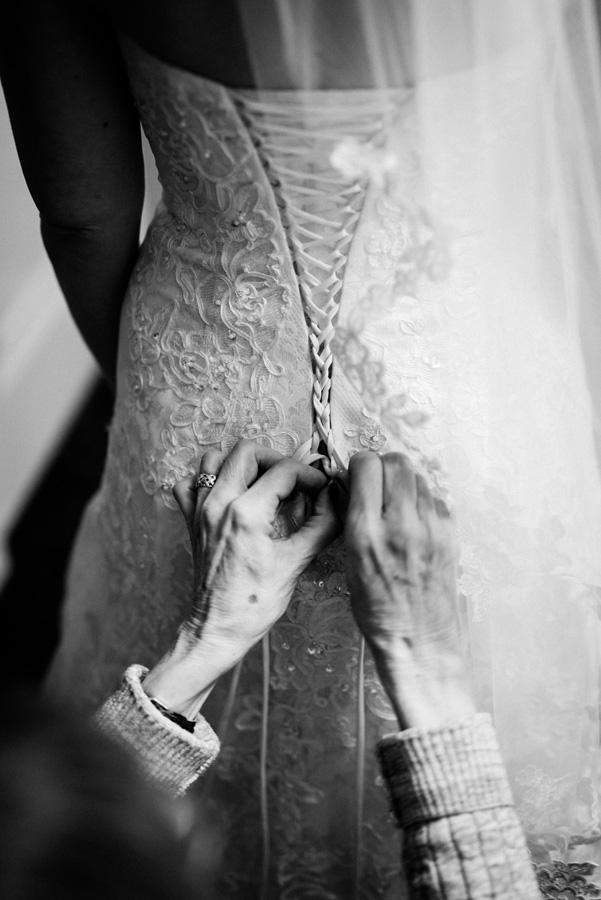 Mom helps bride tie up lace.