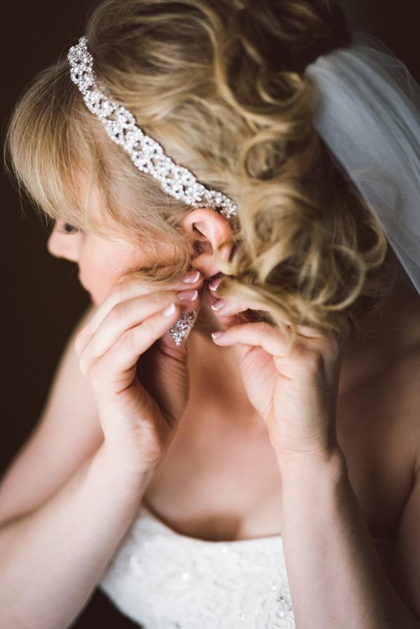 Bride puts her earrings in.