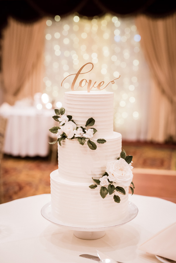 """Wedding cake with """"love"""" topper."""