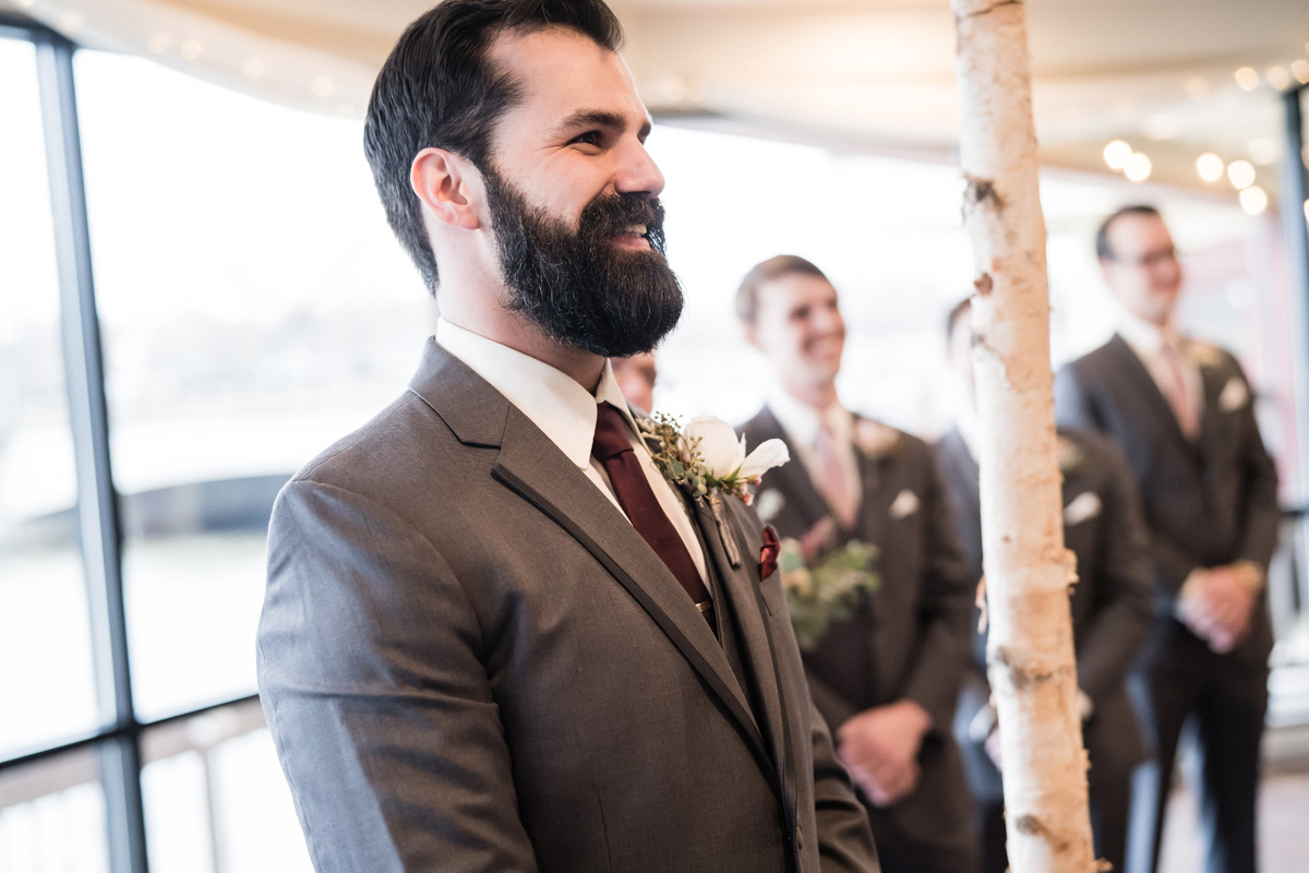 Groom watches his bride walk in during ceremony.