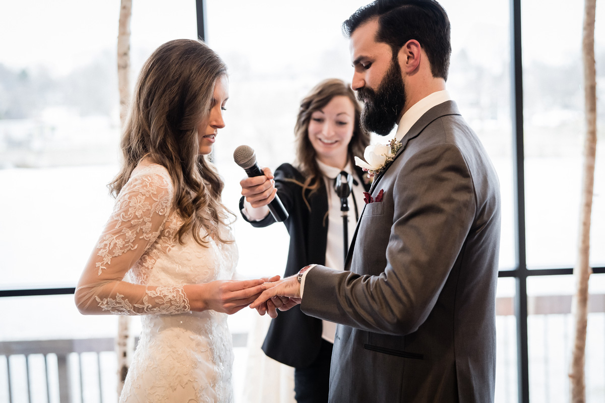 Bride and groom exchange rings during wedding ceremony.