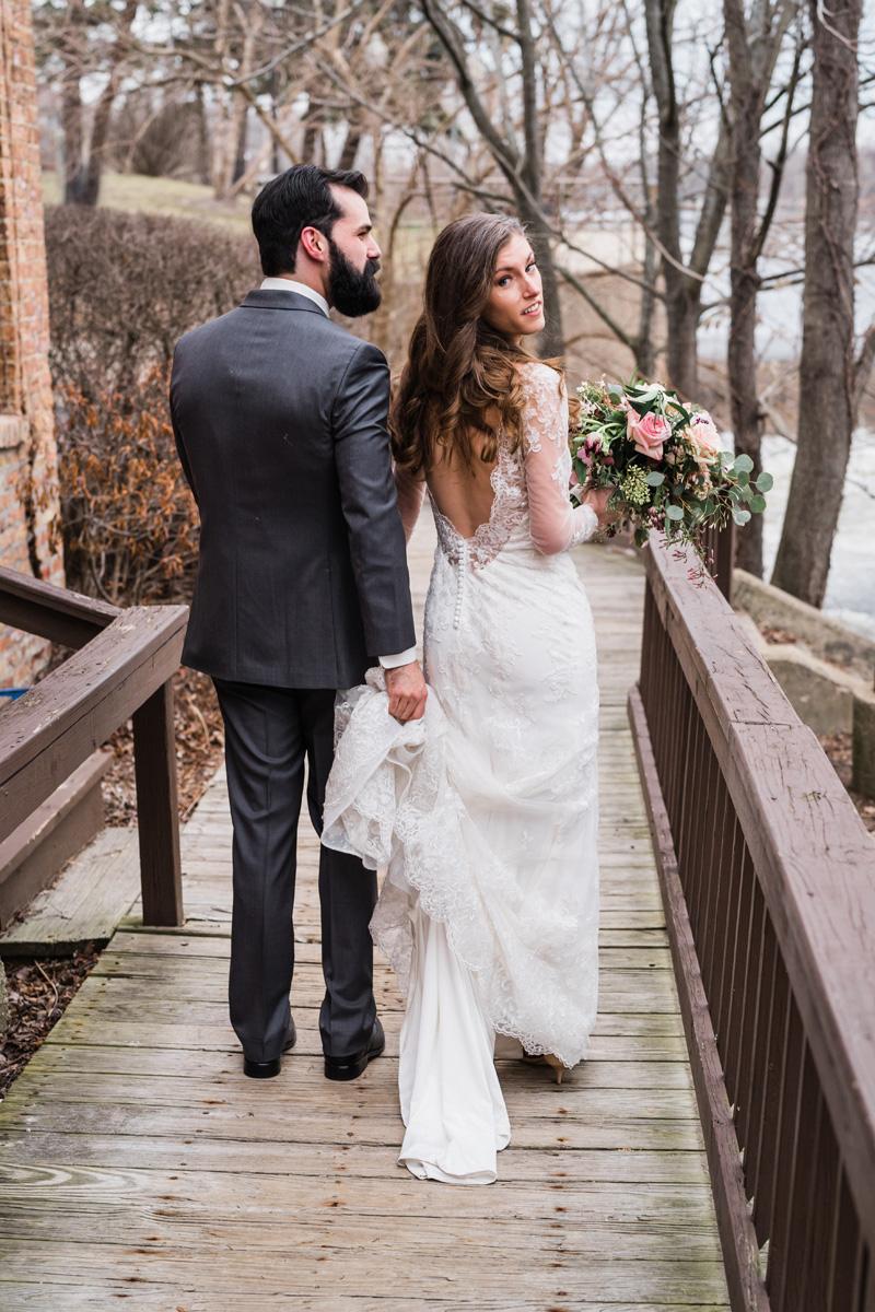 Bride and groom walk across bridge.