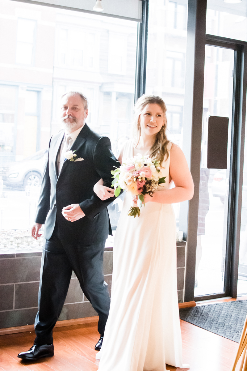 Bride and her dad walk together at wedding ceremony.