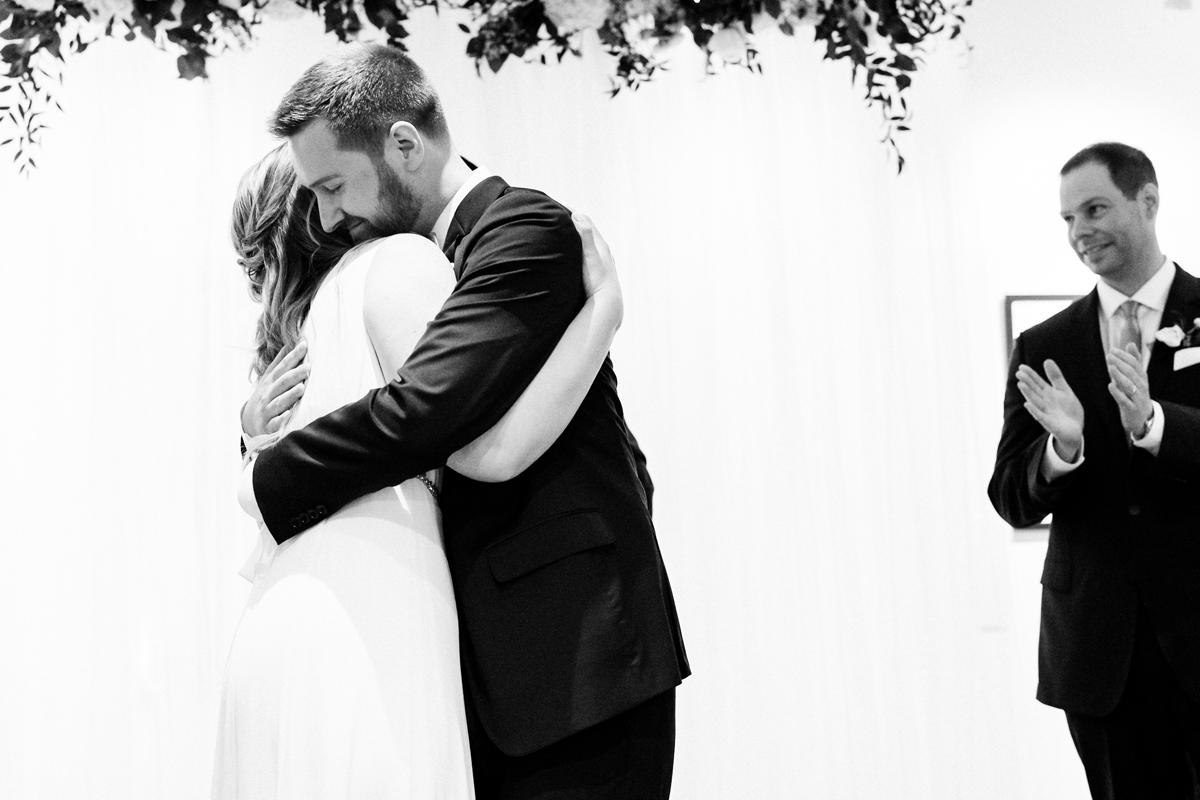 Bride and groom exchange hug at wedding ceremony.