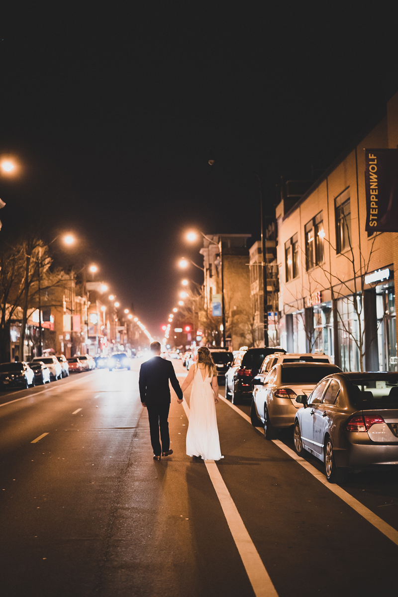 Bride and groom walk down Halsted at night.