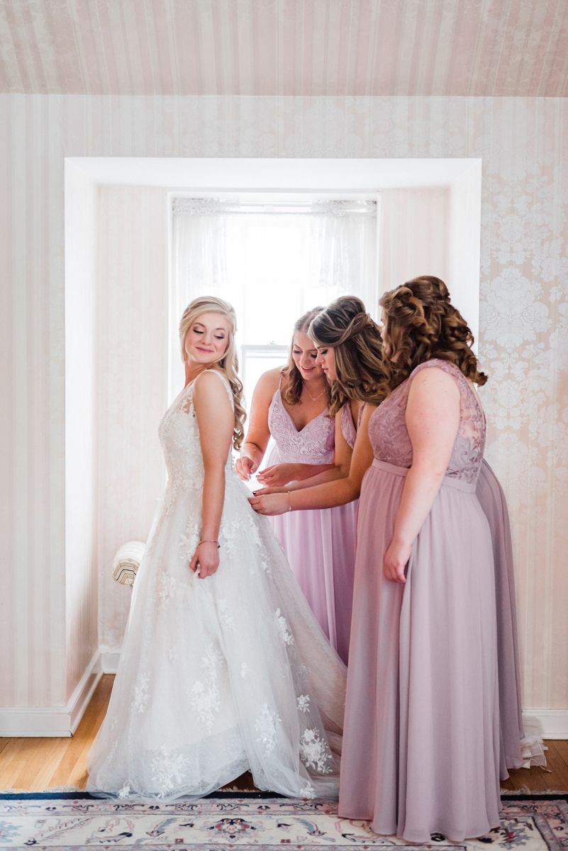 Bridesmaids help bride get ready.
