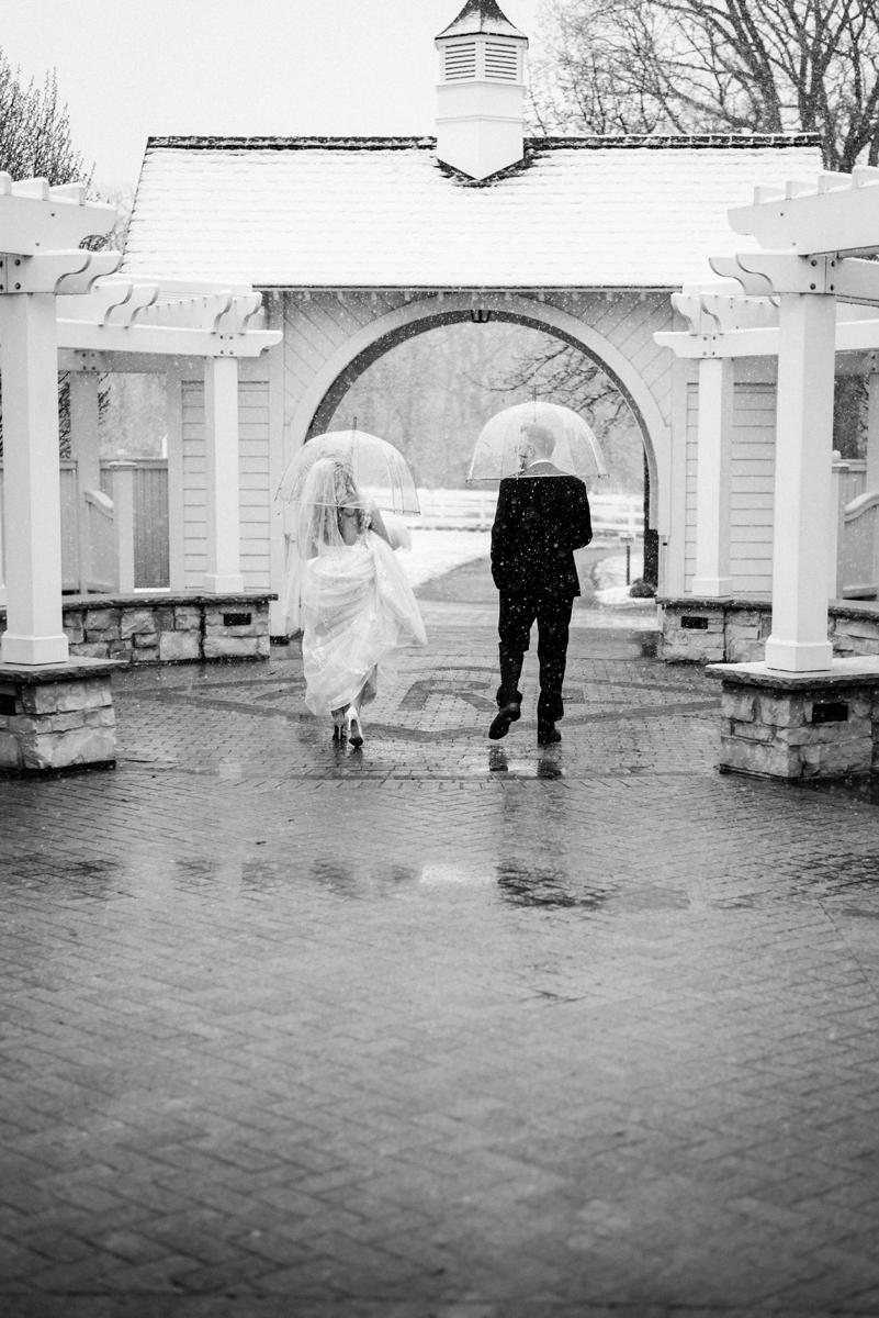 Bride and groom walking through snow.