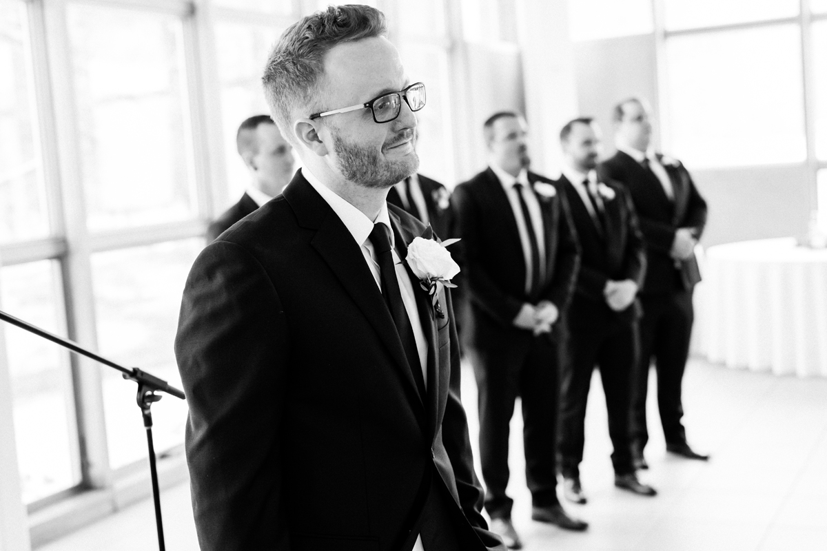 Groom watches his bride walk down the aisle.