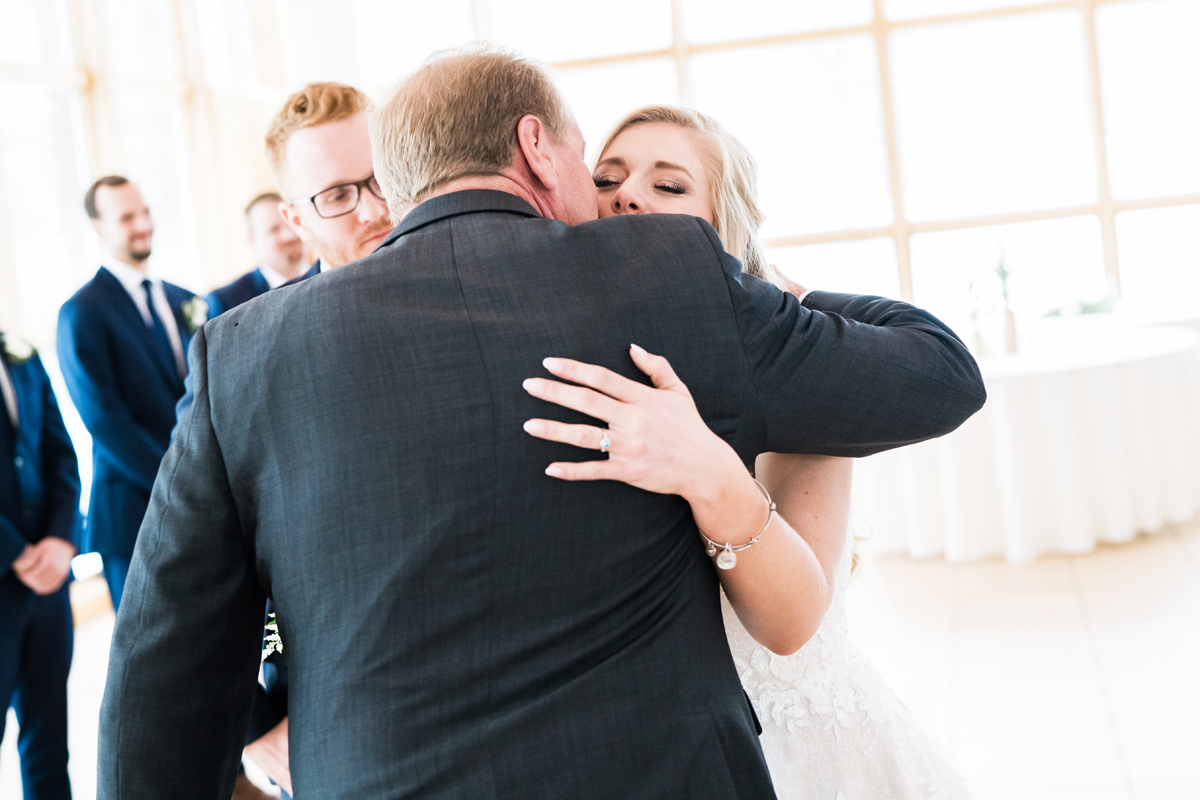 Dad embraces his daughter at wedding ceremony.