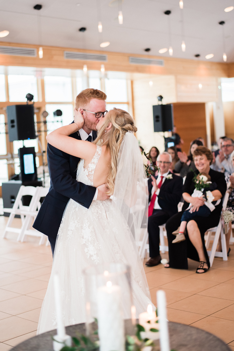Bride and groom kiss at wedding ceremony.