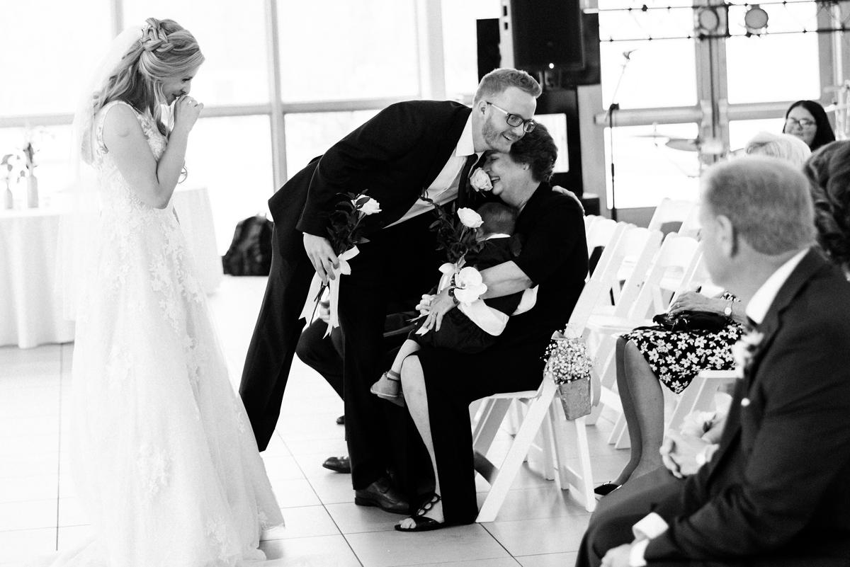 Groom hugs his mom at wedding ceremony.