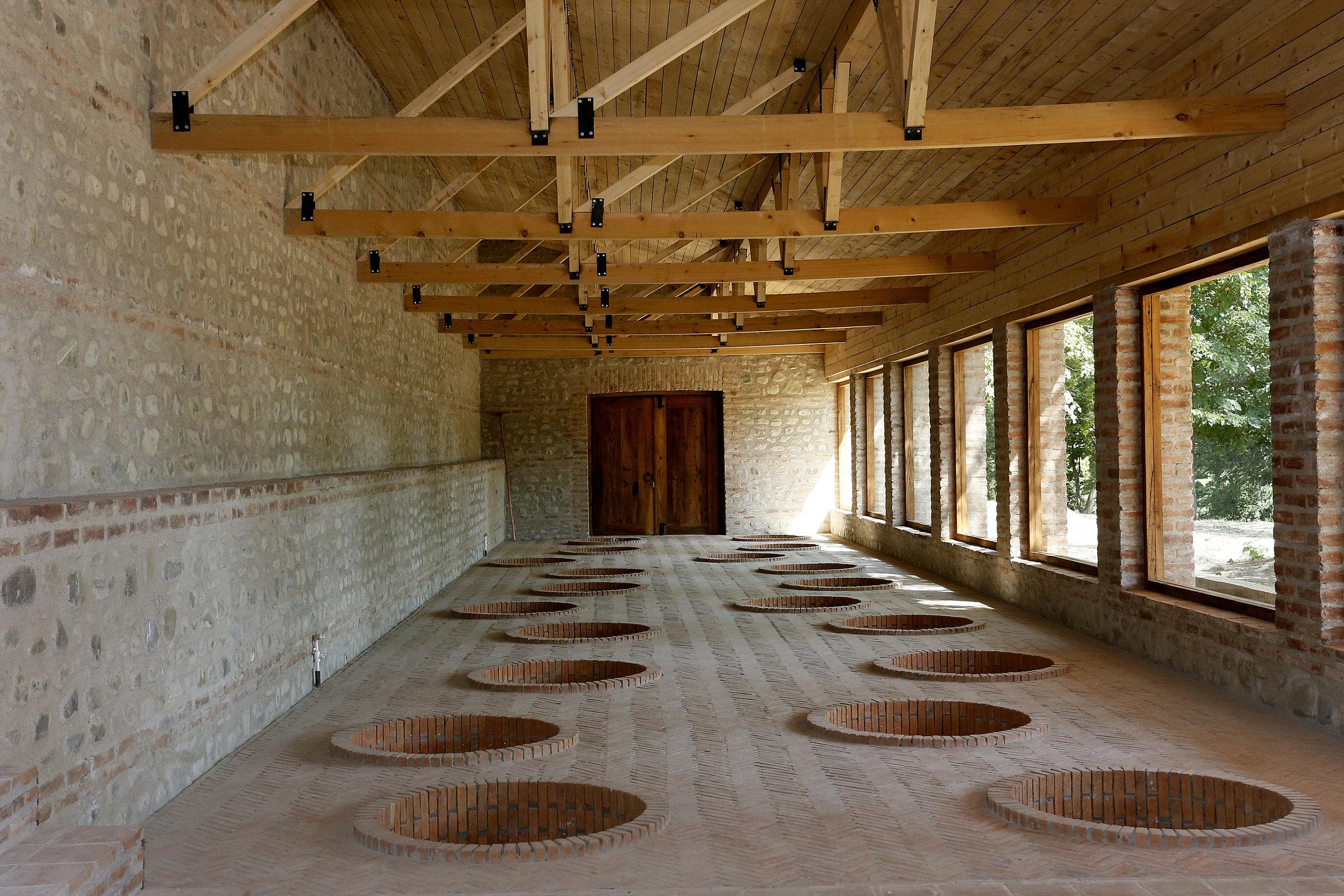 Inside a marani or cellar where a number of qvevri are buried underground to ferment organic Georgian wine