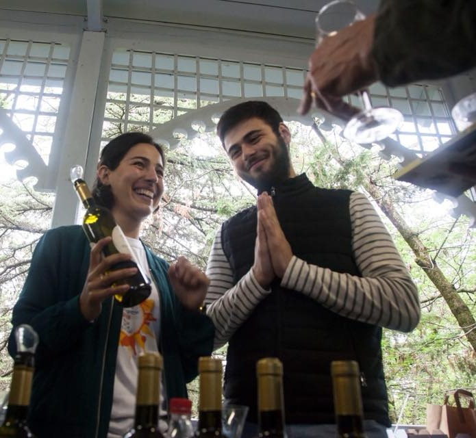 Baia and her brother pour Baia's organic wine at a tasting event in Georgia