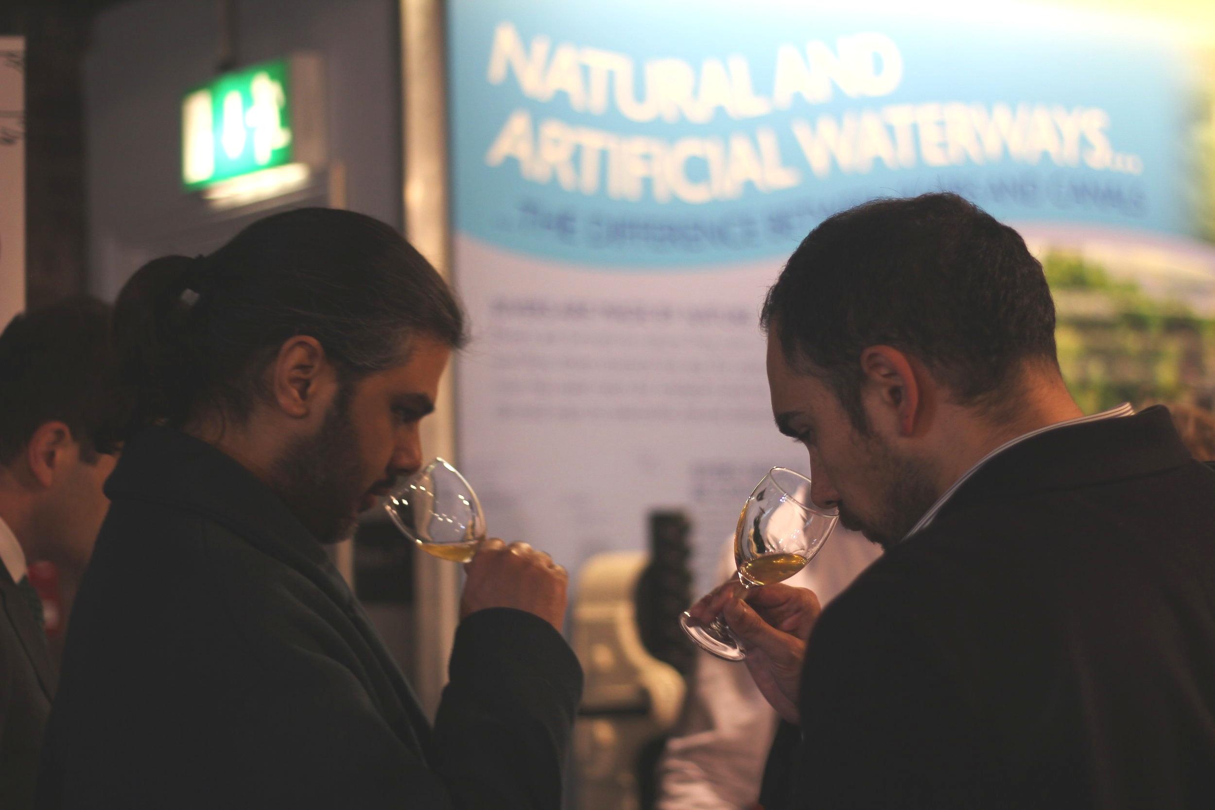 Two gentlemen tasting and smelling Georgian amber or orange wine in the UK