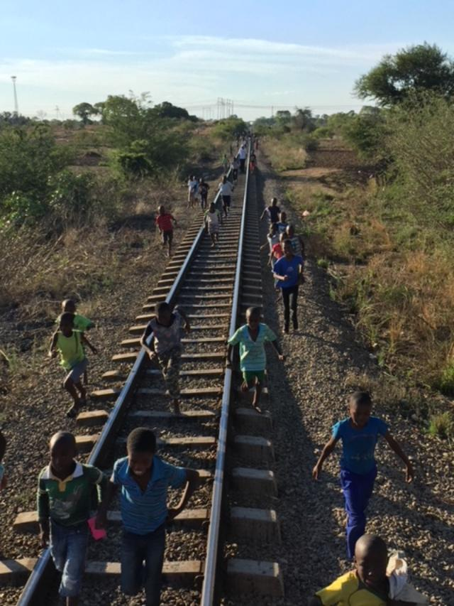 Local children celebrating by trying to keep up with the train!