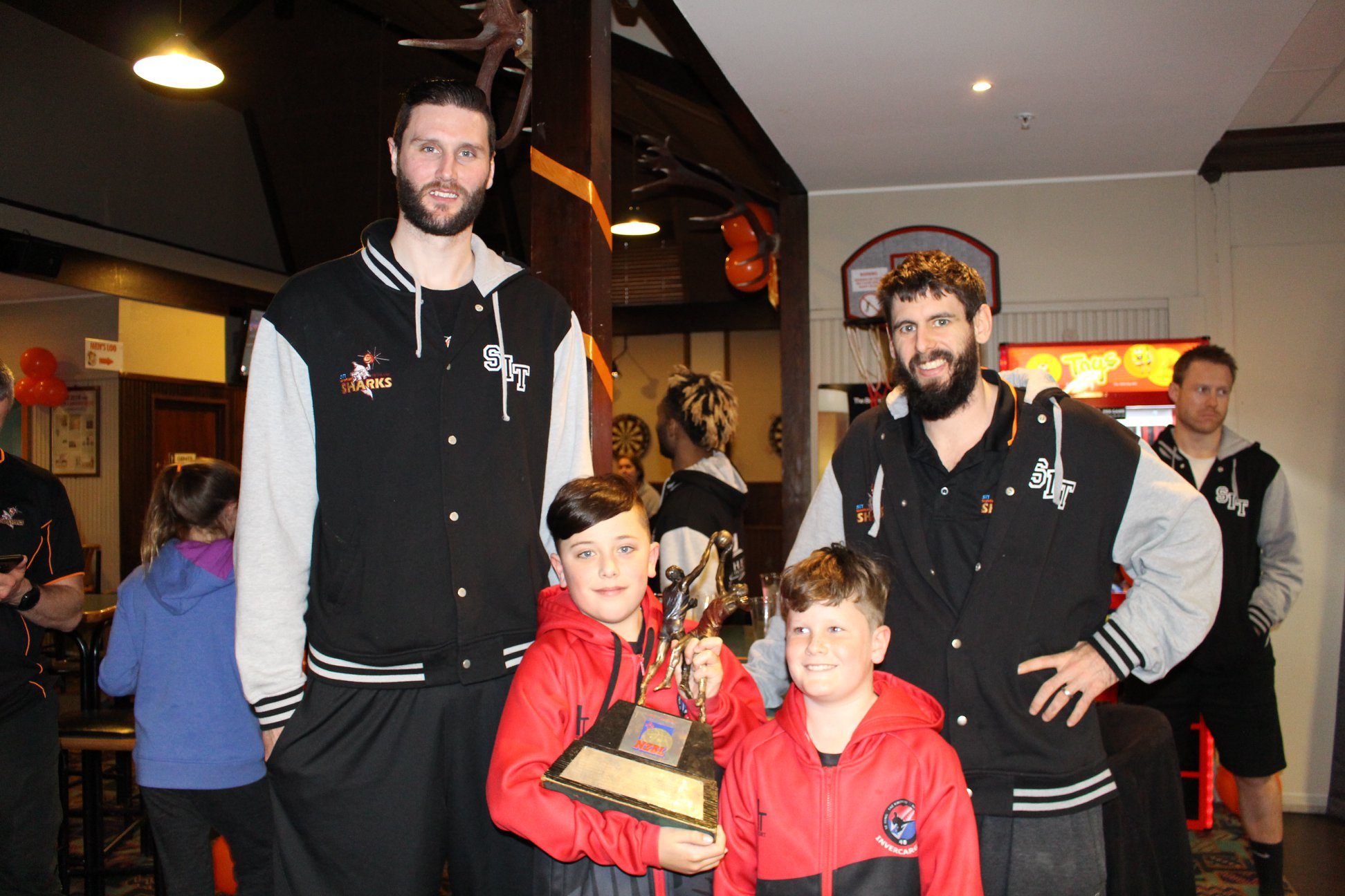 Photo: Alex Pledger, left, and team mate Jarrad Weeks celebrate with young Sharks fans. Pic: Southland Sharks