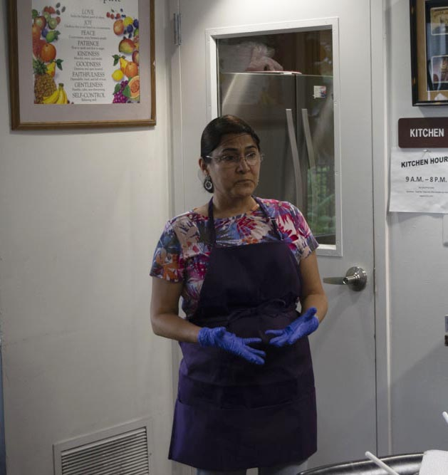 Roots for Life's Cooking and Nutrition Educator Volunteer, Ana Maria, speaks with the ladies of Hyacinth's Place about reading nutritional labels and the benefits of incorporating fresh fruits and vegetables into their diets.
