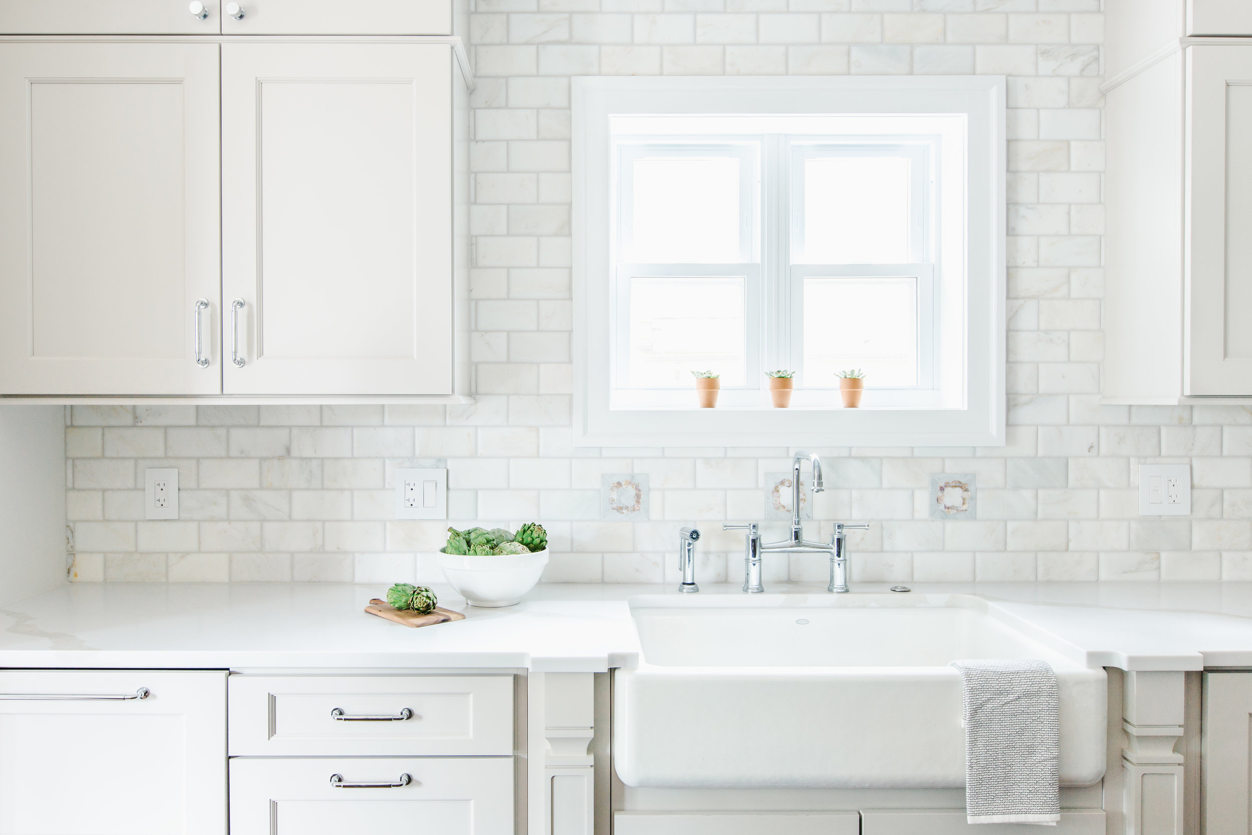 Creamy White Kitchen with Inset Accent Tile and Marble Backsplash