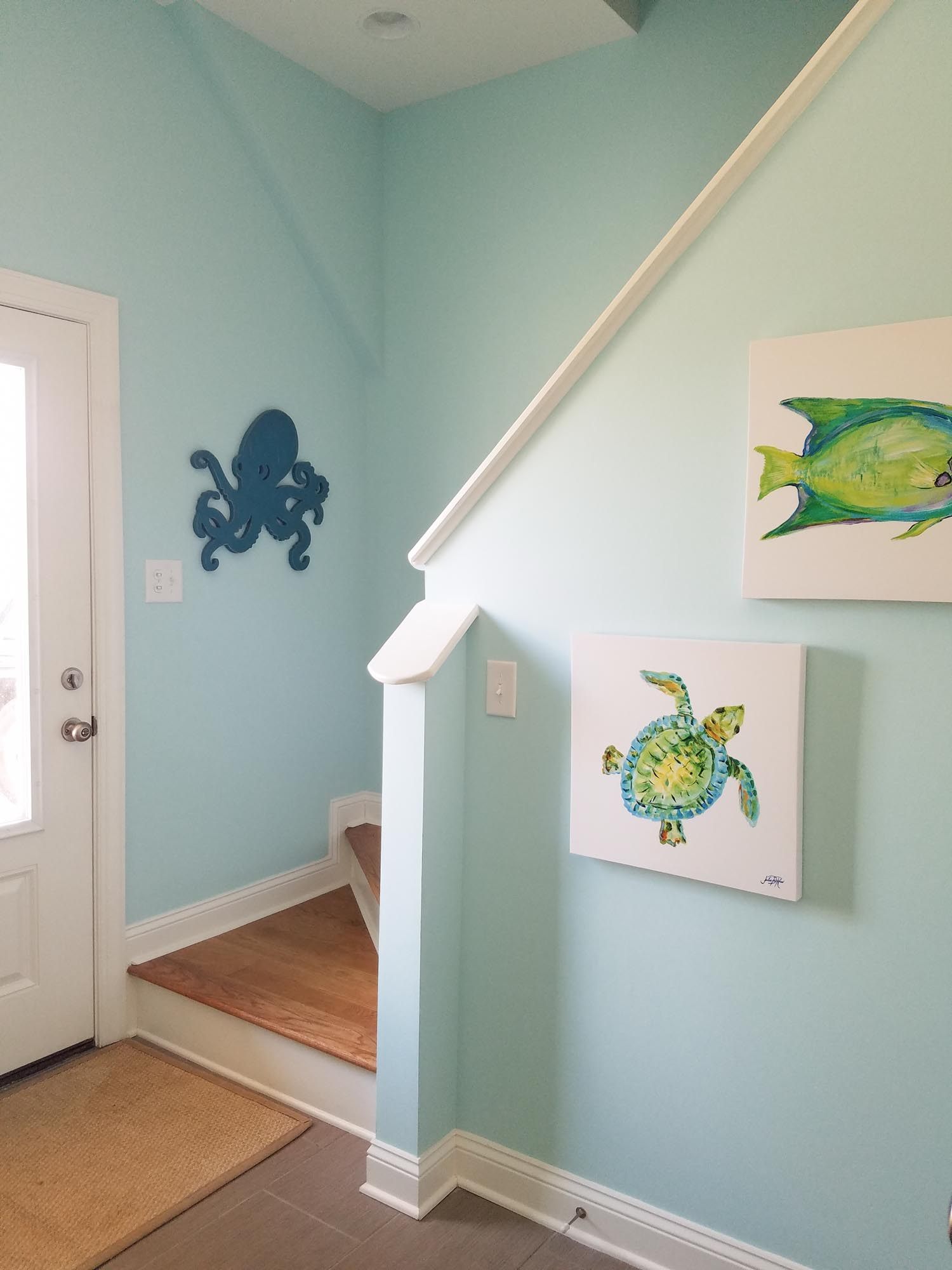 Entry way with coastal themed hanging art