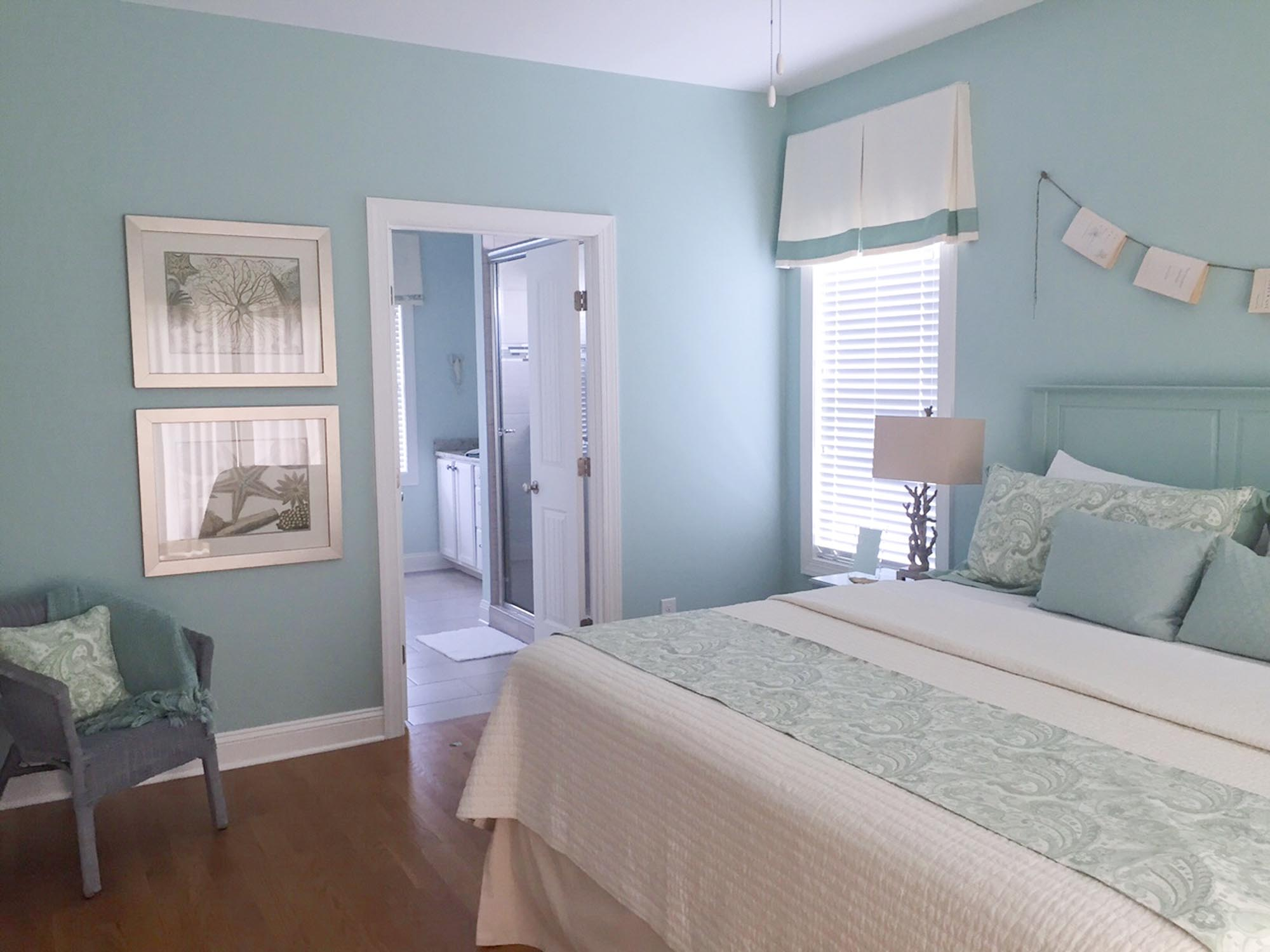 Master bedroom with coastal fabrics and books hanging on a string