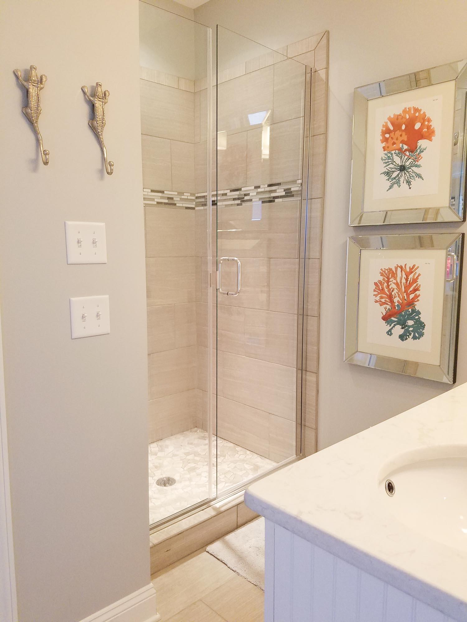 Grey tile shower with glass door gator themed towel hooks