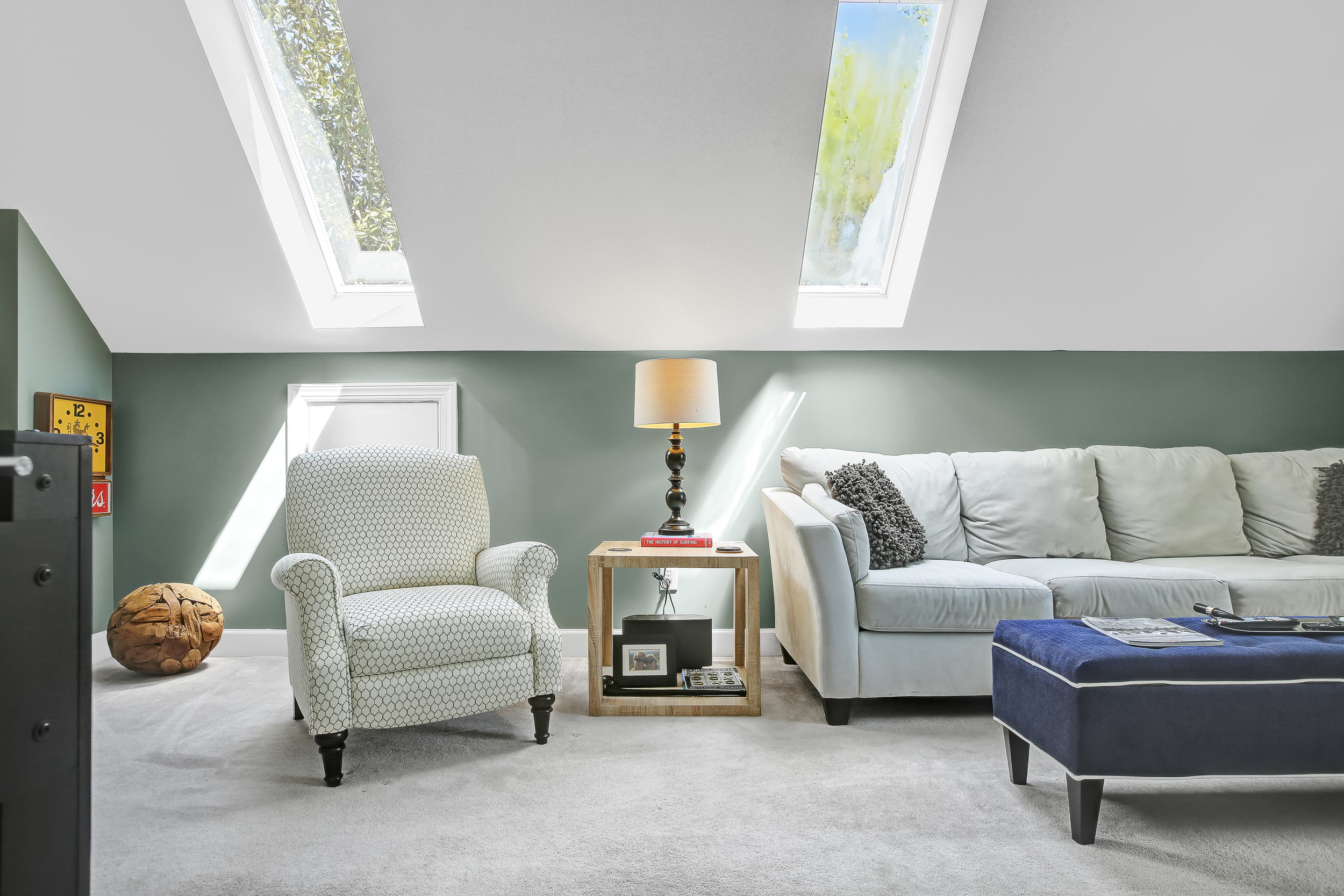 Bonus room with grey sectional and slender skylights
