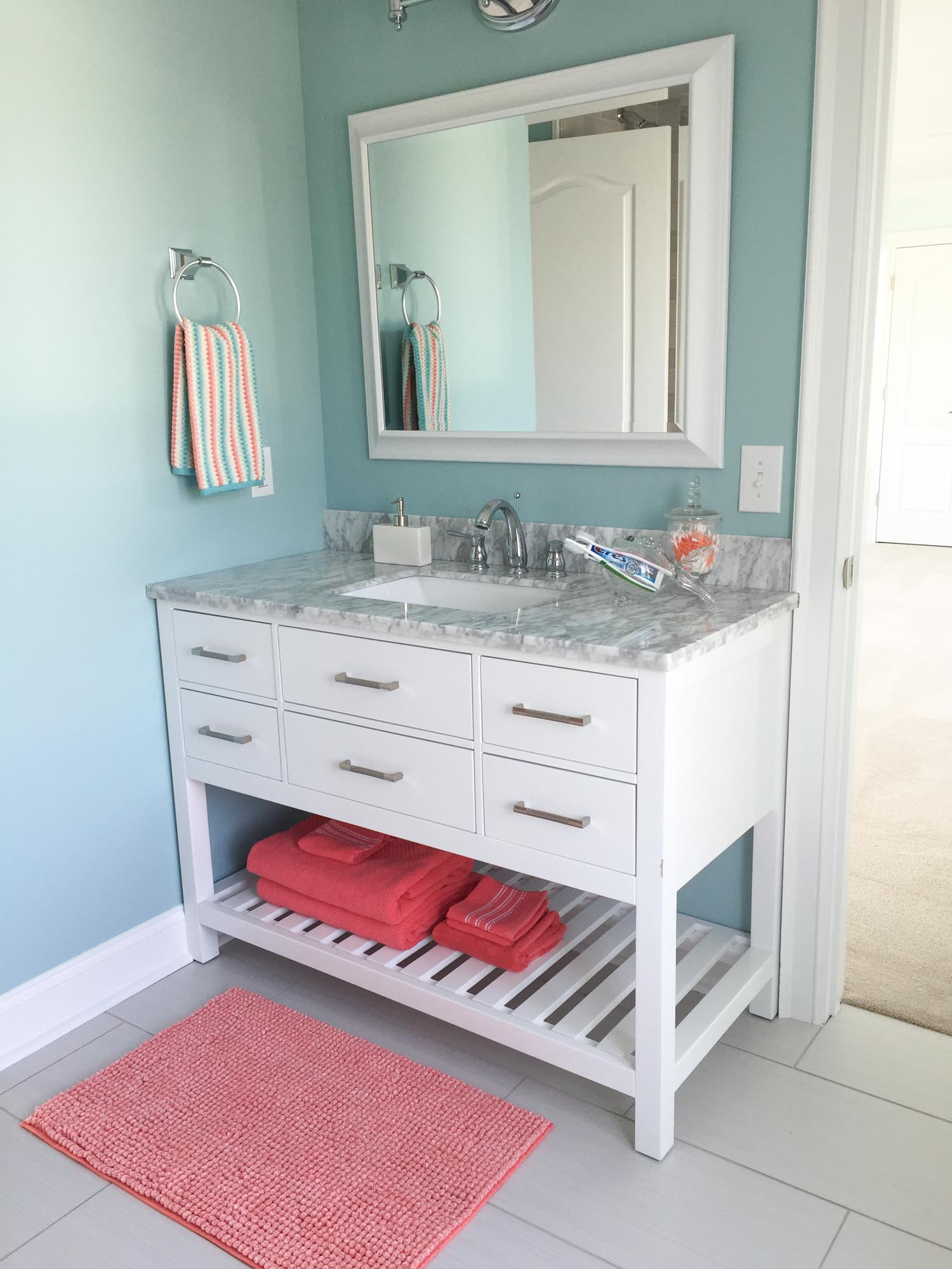 Vanity with coral colored towels and rug