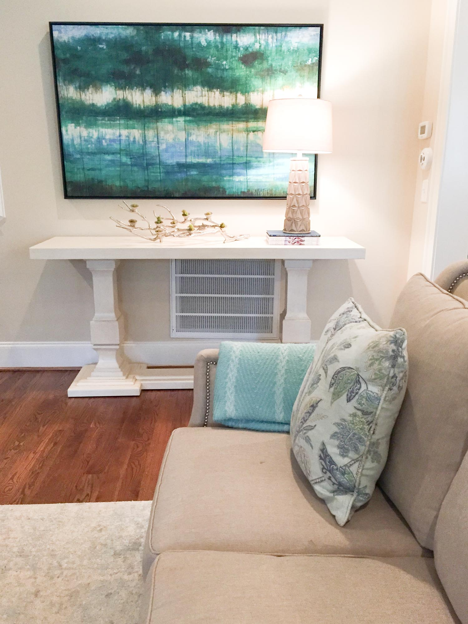 White console with abstract landscape art