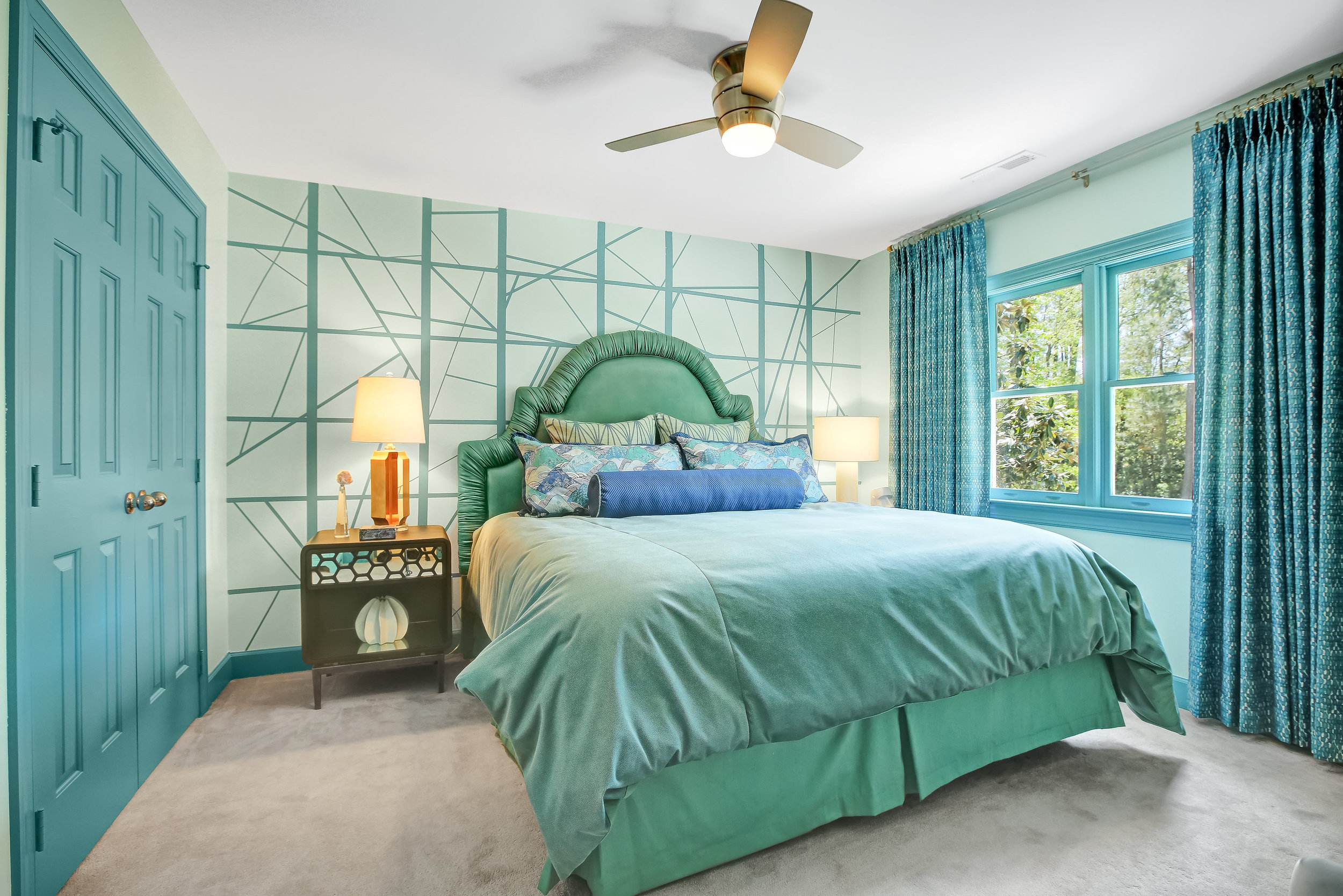 Turquoise colored bedroom with geometric designed wallpaper